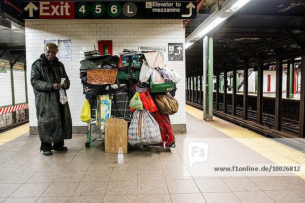 New York  USA. Elder African American homeless man with his cart and belongings  chanting from the bible at a Union Subway Station platform.