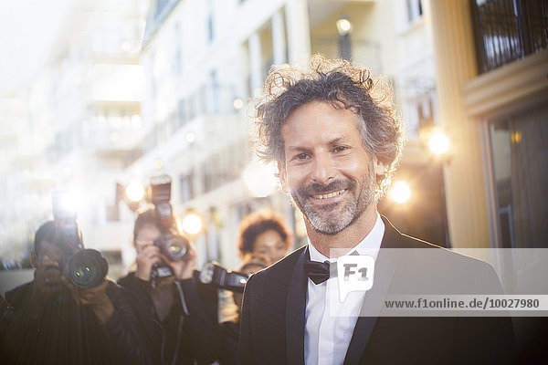 Porträt einer Berühmtheit bei der Veranstaltung mit Paparazzi im Hintergrund