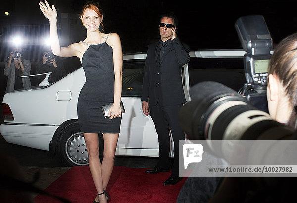 Paparazzi fotografiert lächelnde Berühmtheit beim Eintreffen auf der Veranstaltung