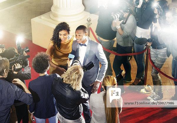 Prominentenpaar wird auf rotem Teppich interviewt