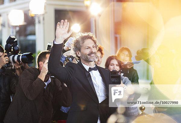 Prominente winken für Paparazzi bei der Veranstaltung