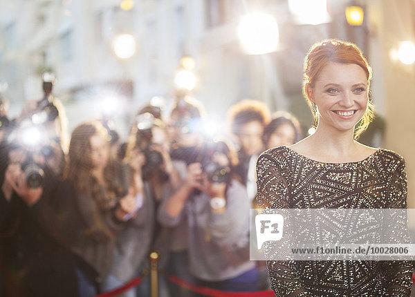 Lächelnde Berühmtheit bei der Veranstaltung mit Fotografieren von Paparazzi im Hintergrund