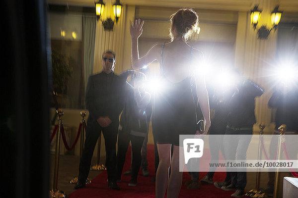 Silhouette einer Berühmtheit in schwarzem Kleid, die bei der Veranstaltung ankommt und den Paparazzi-Fotografen winkt