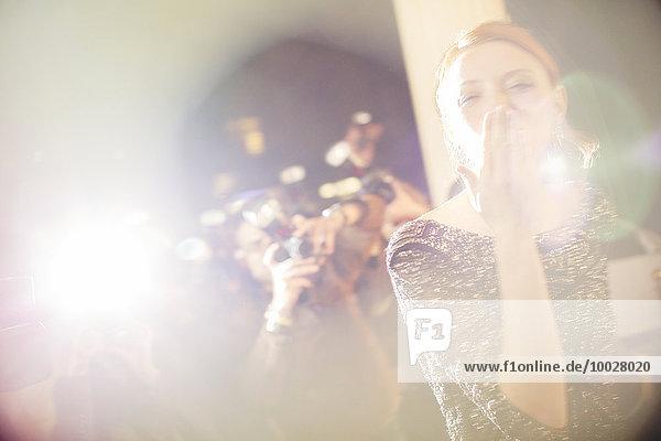 Berühmtheit  die Paparazzi-Fotografen einen Kuss gibt.
