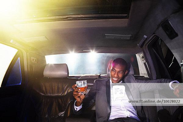 Prominenter Trinkcocktail in der Limousine außerhalb der Veranstaltung