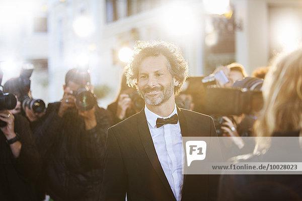Lächelnde Berühmtheit, fotografiert von Paparazzi bei der Veranstaltung