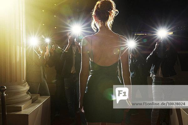 Silhouette einer Berühmtheit in schwarzem Kleid  fotografiert von Paparazzi