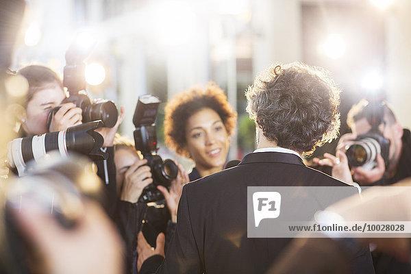 Berühmtheit wird von Paparazzi auf der Veranstaltung interviewt und fotografiert.