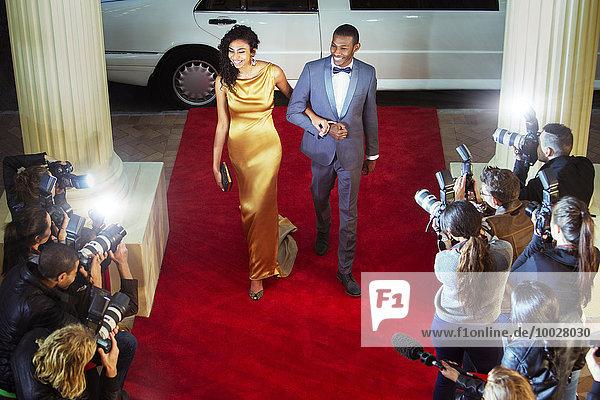Promi-Paar bei der Ankunft auf dem Roten Teppich und fotografiert von Paparazzi