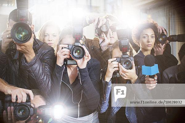 Porträt seriöser Paparazzi-Fotografen  die auf Kameras zeigen