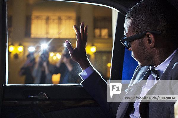 Prominente in der Limousine winkende Paparazzi-Fotografen