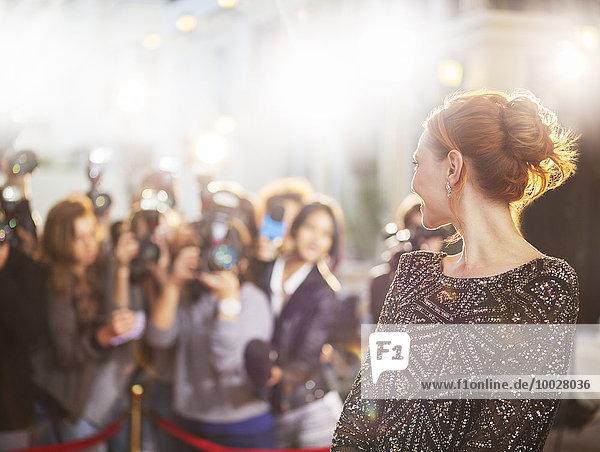 Prominente drehen sich um und lächeln Paparazzi-Fotografen bei der Veranstaltung an.