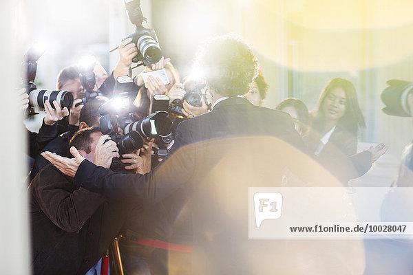 Berühmtheit, die von Paparazzi bei der Veranstaltung fotografiert wird.