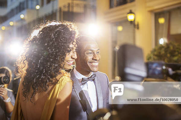 Lächelndes Promi-Paar wird von Paparazzi bei der Veranstaltung interviewt und fotografiert.