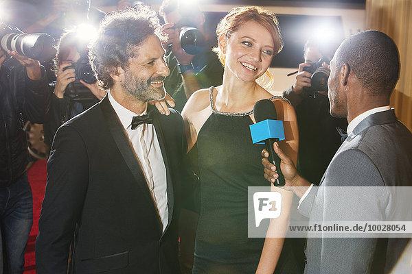 Prominentenpaar wird von Paparazzi bei der Veranstaltung interviewt und fotografiert