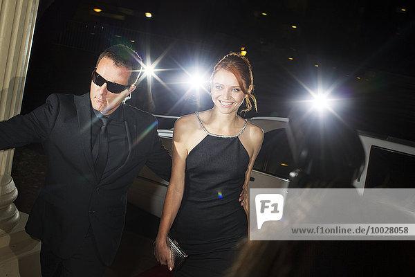 Bodyguard begleitet lächelnde Berühmtheit bei der Ankunft auf der Veranstaltung