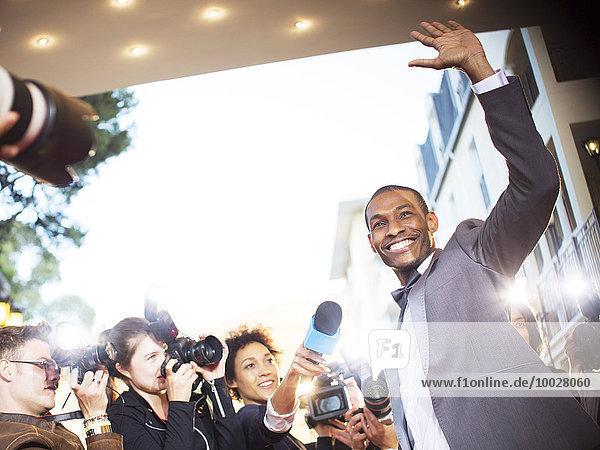 Winkende Berühmtheit wird von Paparazzi auf der Veranstaltung interviewt und fotografiert.