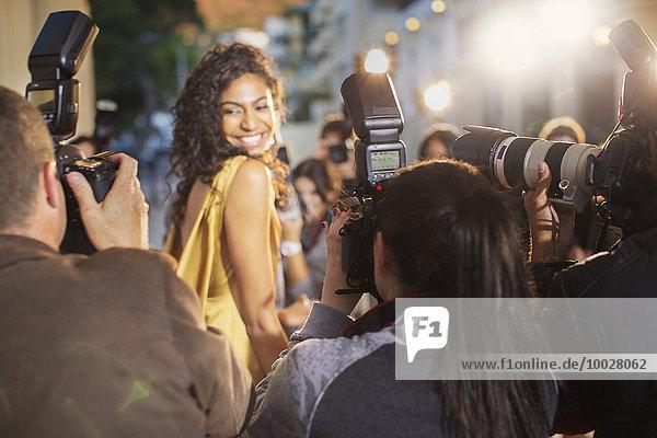 Lächelnde Berühmtheit wendet sich dem Fotografieren von Paparazzi-Fotografen zu.