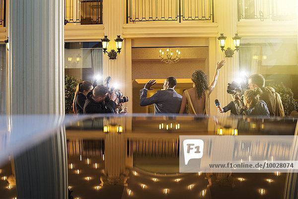 Promi-Paar kommt an und winkt den Paparazzi-Fotografen bei der Veranstaltung zu.