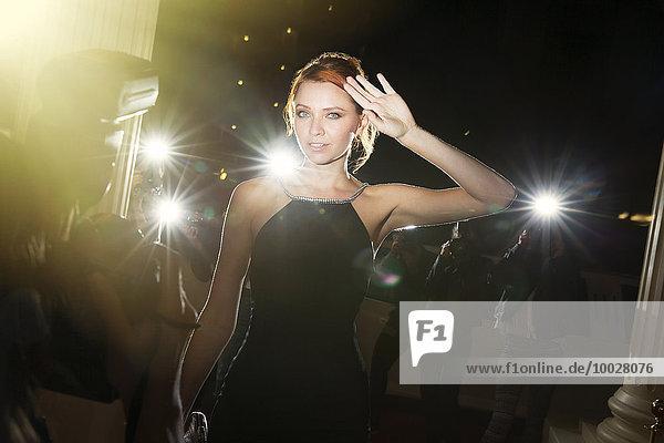 Porträt einer selbstbewussten Berühmtheit  die von Paparazzi bei der Veranstaltung fotografiert wird.