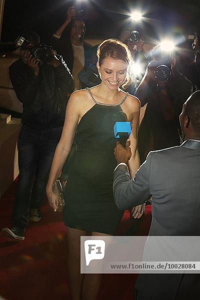 Prominente werden von Paparazzi-Fotografen beim Red Carpet Event interviewt und fotografiert.