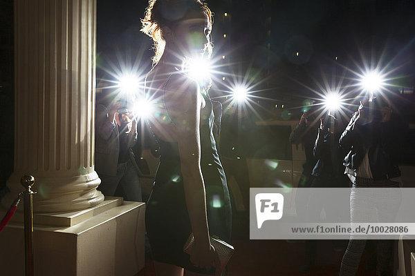 Silhouette einer Berühmtheit  die von Paparazzi-Fotografen bei der Veranstaltung fotografiert wird.