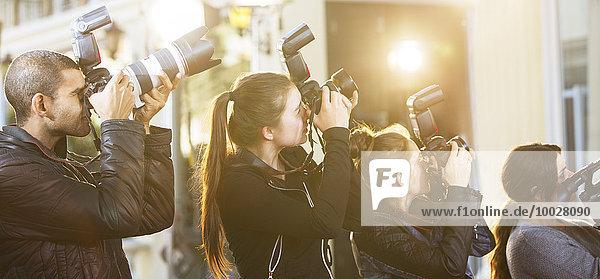 Paparazzi-Fotografen in einer Reihe  die Kameras auf die Veranstaltung richten.