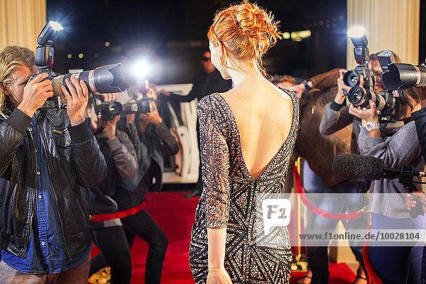 Celebrity verlässt und wird von Paparazzi-Fotografen beim Red Carpet Event fotografiert.