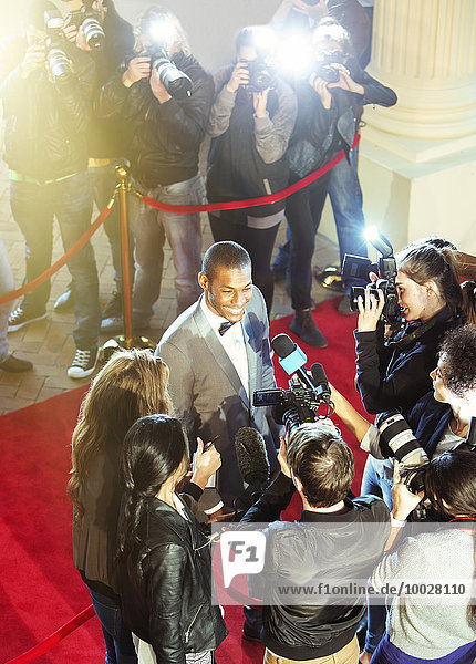 Celebrity being interviewed and photographed by paparazzi photographer at red carpet event
