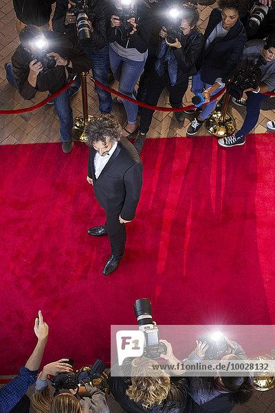 Prominente werden von Paparazzi-Fotografen auf dem roten Teppich fotografiert.