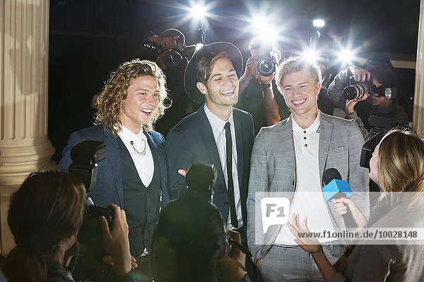 Lächelnde Prominente werden von Paparazzi-Fotografen auf der Veranstaltung interviewt und fotografiert.
