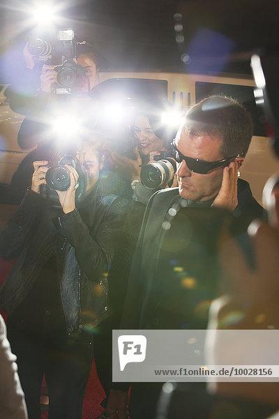 Bodyguard umgeben von Paparazzi-Fotografen bei der Veranstaltung
