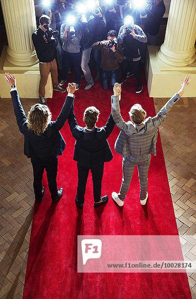 Prominente mit erhobenen Armen für Paparazzi-Fotografen auf dem roten Teppich, Prominente mit erhobenen Armen für Paparazzi-Fotografen auf dem roten Teppich