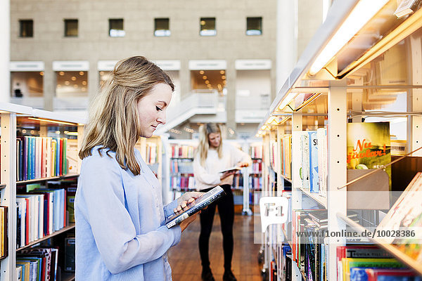 Side view of woman holding book in library