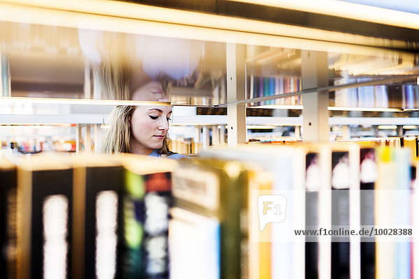Young university student seen through books and shelf in library