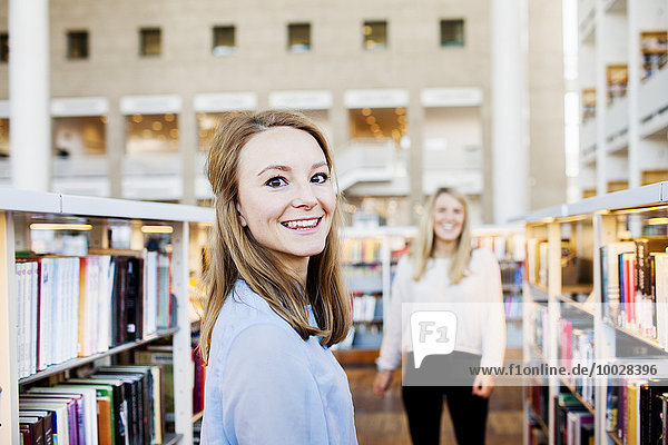 Portrait of young student smiling while female friend standing in background in library