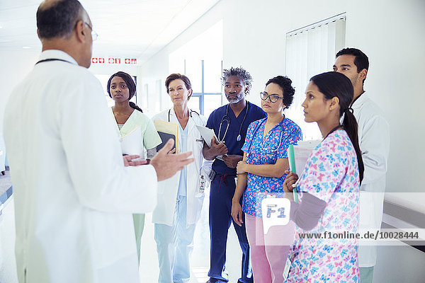 Doctor leading team meeting in hospital corridor