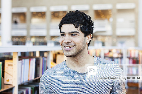 Happy young man looking away in library