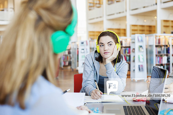 Young woman listening to lecture on laptop at table in library