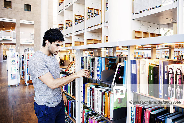 Young man choosing book from shelf in library