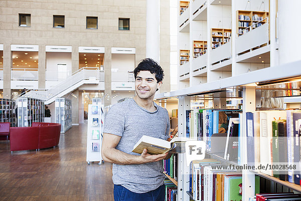 Happy young man looking away while holding book in library