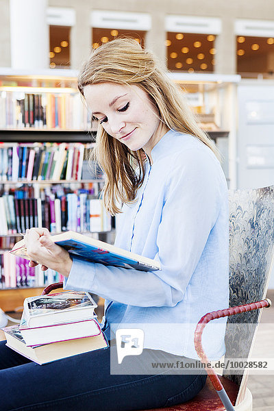 Young woman reading book in library