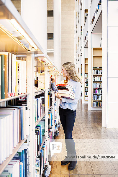 Full length of young woman choosing books from shelf in library