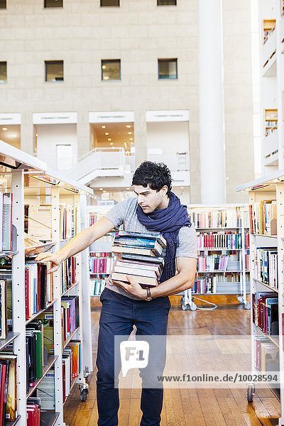 Young man in casuals selecting books in library