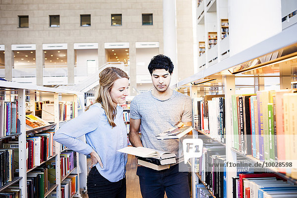 Young friends choosing books in library