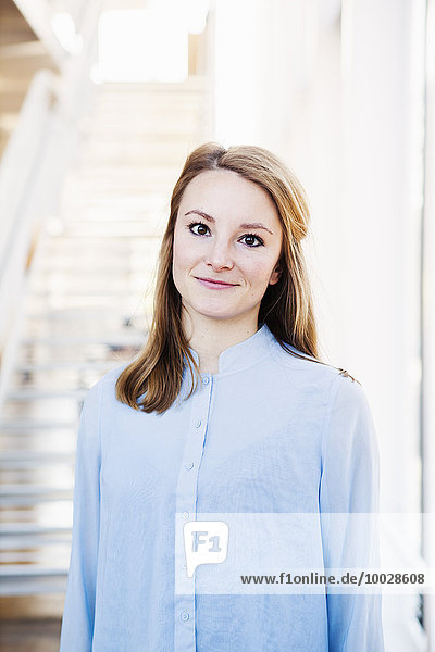 Portrait of confident young woman standing in library