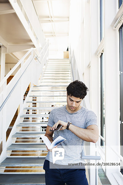 Young man checking time while holding book at staircase in library