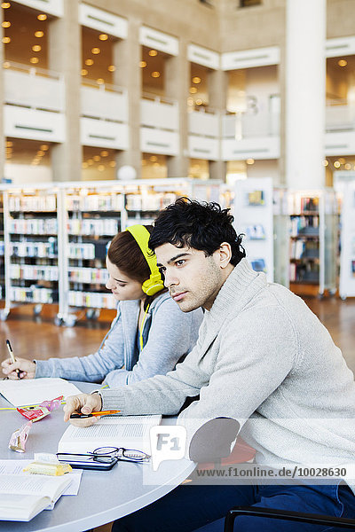 Thoughtful young man looking away while friend reading notes at table in library