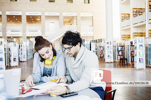 Friends reading book together at table in library