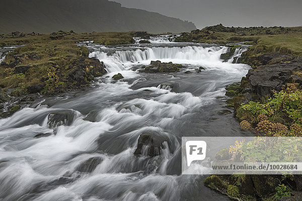 Waterfall through remote landscape  Vik  Iceland